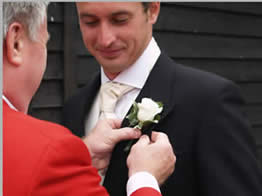 English Toastmaster at Vaulty Manor, Essex UK assisitng the groom with his button hole