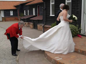 English toastmaster at Vaulty Manor, Essex UK assisting a bride with her wedding dress